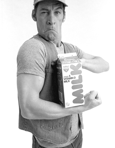 Ernest in Green's Milk ad, flexing muscle