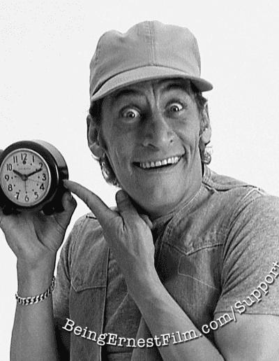Ernest holding a clock with the BeingErnestFilm.com website overlaid.
