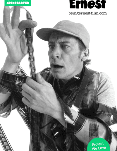 """Ernest holding a filmstrip with the Kickstarter """"Just Funded"""" banner above him and the #ProjectsWeLove bug in the corner."""